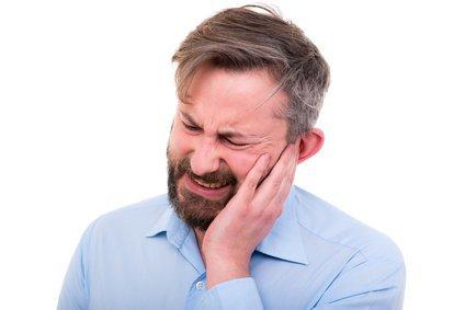 Mann hält sich die Wange mit schmerzverzerrtem Gesicht